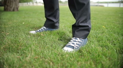 Close up, the feet  in sneakers stand down on the grass Stock Footage