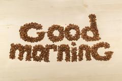 Phrase good morning made with coffee beans on a table top view Stock Photos