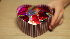 Woman's hands open box with present for Valentine's Day Stock Footage