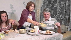 Elderly mother arranges food on plates for family members, evening dinner Stock Footage