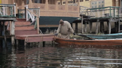 Dal Lake-Jammu & Kashmir  A man goes to the houseboat - stock footage