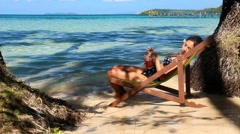 Woman having a drink on a sun lounger by the sea Stock Footage