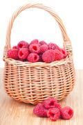 ripe raspberry in a wattled basket,  on a white background - stock photo