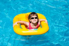 Cute girl swims in a pool in a yellow life preserver Stock Photos