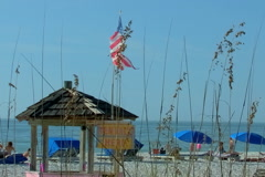 Flag and umbrellas along Clearwater Beach Stock Footage