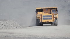 A large multi-ton dump truck with coal into open pit mine - stock footage