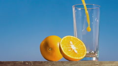 Pouring a glass of orange juice creating splash Stock Footage