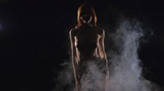 Young girl posing (nude, naked) in smoke - stock footage