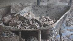 Building demolition waste old concrete thrown into a wheelbarrow Stock Footage