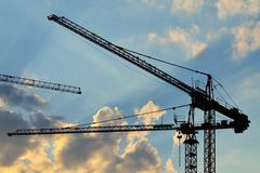 silhouettes construction cranes - stock photo