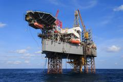 Offshore jack up drilling rig over the production platform in the middle of t Stock Photos