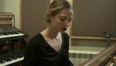 4K beautiful girl playing the piano in a recording studio light slow motion Stock Footage