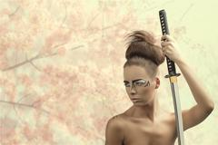 brunette in japan style with katana looks at right - stock photo