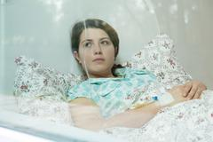Ill woman in bed Stock Photos
