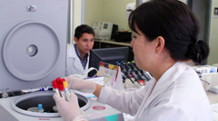 Mexico, 2014: BACK SHOULDER. Woman put blood test tubes in a machine. Stock Footage