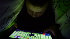 Young Boy Uses A Digital Tablet Under The Covers Stock Footage