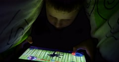 Young Boy Uses A Digital Tablet Under The Covers 4k Stock Footage