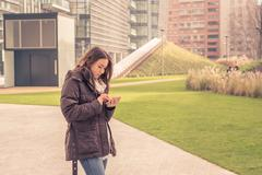 Young beautiful girl texting in the city streets Stock Photos