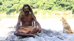 Indian sadhu, poor man sits along the Ganges river in Rishikesh, India Stock Footage