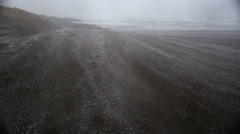 Snow carried by wind swirling across a sandy beach, Sandvik, Iceland Stock Footage