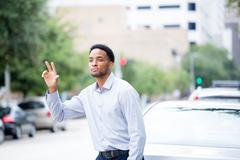 Closeup portrait, young man in blue shirt , raising hand to say hi, goodbye o Kuvituskuvat