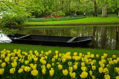 Spring garden with canal and boat Stock Photos