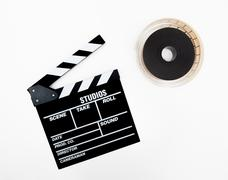 Clapper and 35mm reel isolated Stock Photos