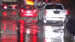 Vehicles drive through flood waters Stock Footage