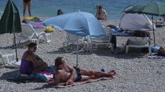 Primosten sunbathing on the beach Stock Footage