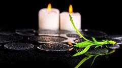 beautiful spa still life of green twig bamboo and candles on zen basalt stone - stock photo