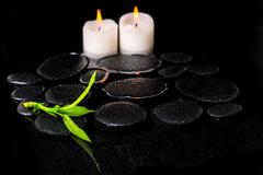 beautiful spa background of green branch bamboo and candles on zen basalt sto - stock photo