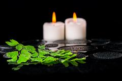 beautiful spa concept of green branch adiantum fern with drops and candles on - stock photo