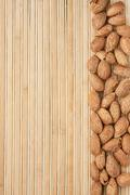 unpeeled almonds lying on a bamboo mat - stock photo