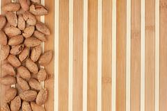Unpeeled almonds lying on a bamboo mat Stock Photos