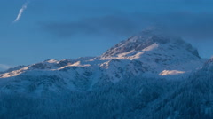 Sunrise in the alps - snow mountain landscape with fir forest timelapse zoom out Stock Footage