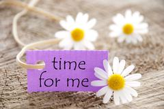 Purple label with life quote time for me and marguerite blossoms Stock Photos