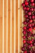 cherry lying on bamboo mat - stock photo