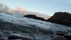 120 fps footage of smooth rocks above and below water as waves hits the camera Stock Footage