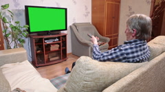 Mature Caucasian man changing tv channels with two remotes while watching tvset  Stock Footage