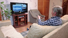 Caucasian senior man watching tv on sofa in domestic room, changing channels Stock Footage