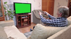 Caucasian senior man watching tv with green screen on sofa in domestic room, cha Stock Footage