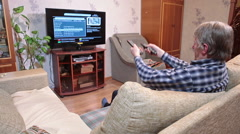 Mature man changing tv channels with two remotes while watching tvset in living  Stock Footage