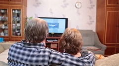 Senior parents watching tv in living room, sitting together on sofa - stock footage