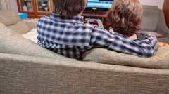 Mature couple sitting in front of tv with remote control in hands, daughter comi Stock Footage