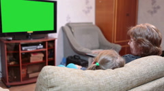 Mother and her daughter watching green screen tv in living room together Stock Footage