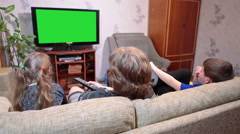 Mature mother with son and daughter watching on greenscreen tv when sitting - stock footage
