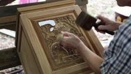 Stock Video Footage of Man cuts a picture with elephants out of wood at a teak factory in Thailand