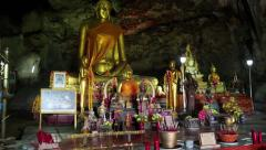 People and Golden Buddha statue inside temple in the cave, Thailand Stock Footage