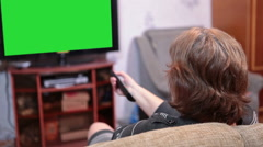 Greenscreen of tvset, woman changing channels using the TV remote - stock footage