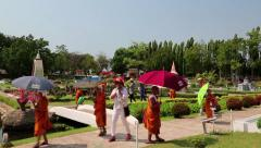 Young buddhists in yellow vestments at excursion in Mini Siam park in Pattaya Stock Footage